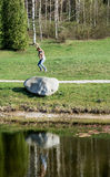 Young woman jumping on the big stone Stock Photo