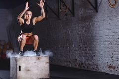 Woman jumping box. Fitness woman doing box jump workout at cross fit gym. stock image