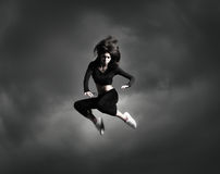 A young woman jumping on a cloudy background Stock Photo