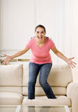Young woman jumping on couch Stock Photo