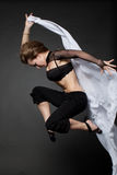 Young woman jumping from a developing tissue. stock photography