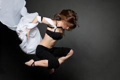 Young woman jumping from a developing tissue. stock image