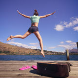 Young woman jumping on a dock Stock Photography