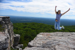 Young woman jumping at the edge of roc at Minnewaska State Park Royalty Free Stock Photos