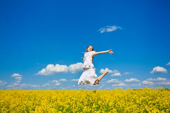 Young woman jumping on field. Beautiful young woman jumping on field in summer Royalty Free Stock Photo