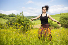 Young woman jumping in a field of flowers Stock Photography