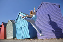 Young Woman Jumping In Front Of Beach Huts Royalty Free Stock Photo