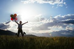 Young woman jumping on grassland with colored balloons Stock Photography