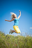 Young woman jumping on   green meadow Royalty Free Stock Images