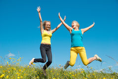 Young woman jumping on green meadow and blue sky Stock Photos