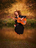 Young woman jumping with guitar Stock Photo