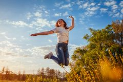 Young woman jumping and having fun in spring field at sunset. Happy and free girl enjoys nature royalty free stock photo