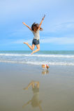 Young woman jumping with her cute jack russel puppy on the beach Stock Photography