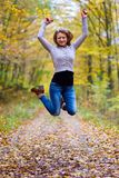 Jump for joy. Young woman jumping high in the air in the forest Stock Image