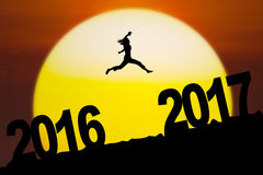 Young woman jumping on the hill with numbers. Silhouette of young woman running and jumping between numbers 2016 to 2017 in the sunset Stock Images