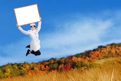 Young woman jumping and holding blank board Royalty Free Stock Photos