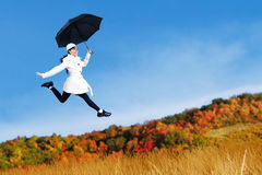 Young woman jumping with holding umbrella Royalty Free Stock Images