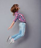 Young woman jumping isolated on a gray Royalty Free Stock Images