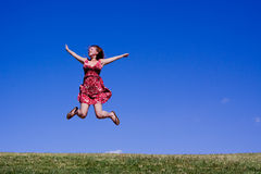 Young woman jumping for joy!. Attractive female jumping high in the air for joy, or success in this summer image Royalty Free Stock Images