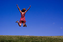 Young woman jumping for joy!. Facing away from the camera, beautiful woman jumping for joy on this green hillside Stock Image