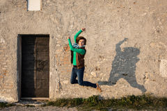 Young woman is jumping for joy in front of the old wall. Young caucasian woman is jumping for joy in front of the old wall stock photography