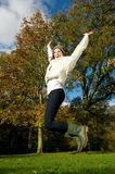 Young woman jumping for joy outdoors on a beautiful fall day Stock Photos