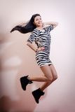 Young woman jumping joyfully in zebra dress and Stock Photo