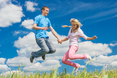 Young woman jumping with a man Stock Image