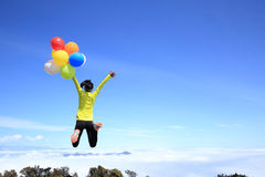 Young woman jumping on mountain peak with colorful balloons Stock Photo