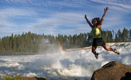 Young woman jumping in nature. Young woman jumping  near waterfall Storforsen in Sweden Stock Photography
