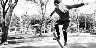Young Woman Jumping Olly Skateboard Concept Royalty Free Stock Images