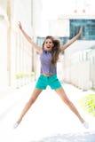 Young woman jumping outdoors Stock Photos
