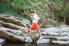 Young woman jumping over the creek Stock Photos