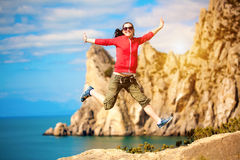 Young woman is jumping over mountain peak Royalty Free Stock Image