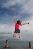 Young woman jumping at the pier Stock Image