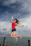 Young woman jumping at the pier Royalty Free Stock Image
