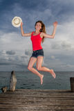 Young woman jumping at the pier Royalty Free Stock Images