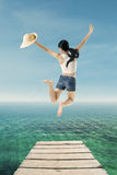 Young woman jumping at pier Stock Photos