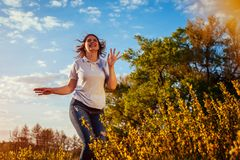 Young woman jumping, running and having fun in spring field at sunset. Happy and free girl relaxes and enjoys nature. And life Royalty Free Stock Photography