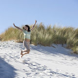 Young woman jumping in sand dunes royalty free stock image