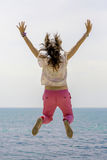 Young woman jumping by the sea Royalty Free Stock Photos