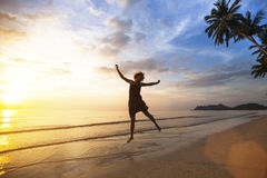 Young  woman jumping on the sea coast during the amazing sunset. Young happy woman jumping on the sea coast during the amazing sunset Stock Photography