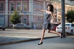 Young woman jumping at the street in city Stock Photo
