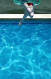 Young woman jumping in swimming pool Stock Image