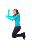 Young woman jumping with thumbs up. Teenage woman jumping showing thumbs up Royalty Free Stock Images