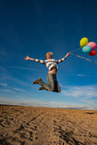 Young woman jumping with toy balloons Stock Photography