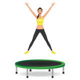 Young woman jumping on trampoline. Pretty fit girl in leggings and crop top with hands up. Stock Images