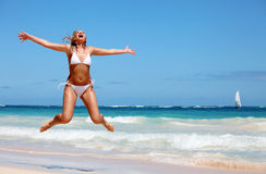 Young woman jumping on tropical beach Stock Photography