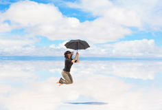Young woman jumping with umbrella Stock Images