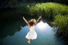 Young woman jumping into the water Royalty Free Stock Photos